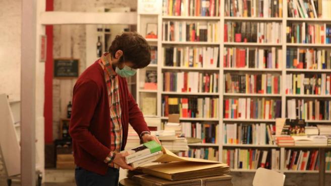Imagen del dueño de una librería preparando pedidos durante el estado de alarma.