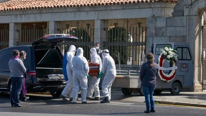 Operarios con trajes de protección se disponen a introducir un ataúd en el cementerio de Ávila.