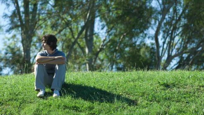 Adolescente sentado en la hierba.