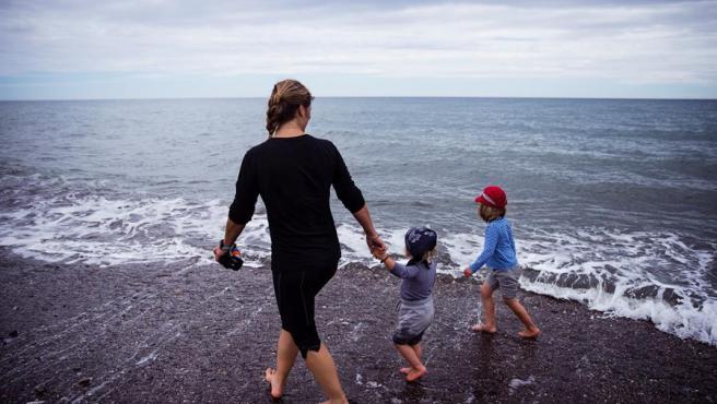 Una mujer con dos niños pasea por la playa de Torre de Benagalbón en Rincón de la Victoria (Málaga).