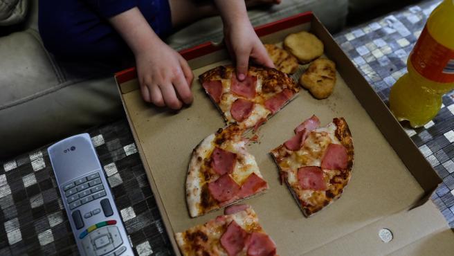 Un niño come pizza del menú infantil de Telepizza mientras ve la televisión en su casa