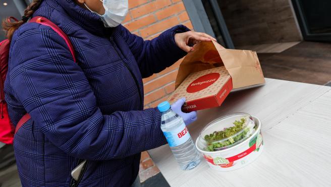 Una mujer protegida con mascarilla y guantes de látex abre el menú infantil de Telepizza en el barrio de San Fermín en el distrito de Usera.
