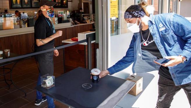 Un cliente recoge un café en una cafetería de Starbucks en McLean, Virginia (EE UU), reabierta tras el levantamiento en el estado de algunas de las restricciones impuestas por la pandemia del coronavirus.