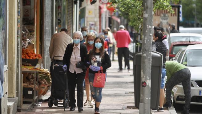 Varias personas con mascarilla en una calle de Madrid.