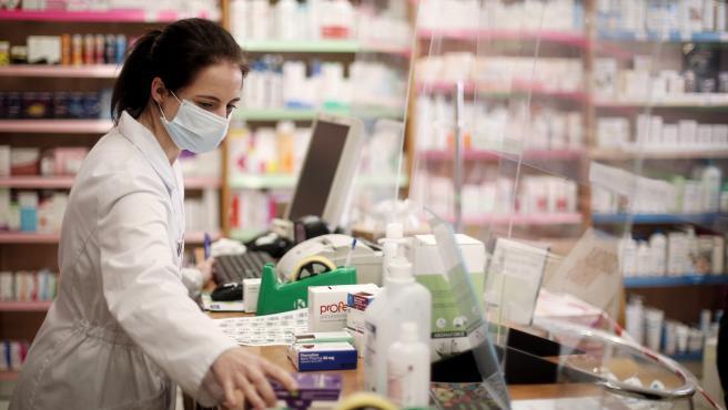 Una farmacéutica con mascarilla despacha en una farmacia. Archivo