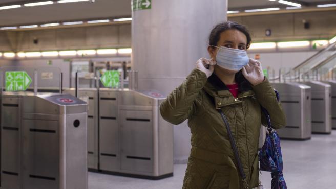 Una mujer se pone una mascarilla tras recibirla de Protección Civil a la entrada del metro