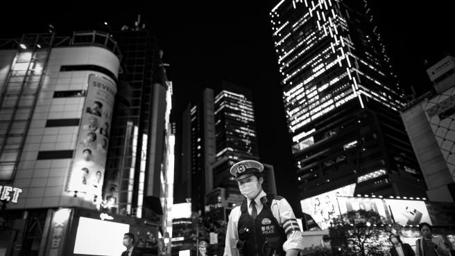 Un policía enmascarado patrulla una de las avenidas del distrito comercial de Shibuya, uno de los más transitados de Tokio, a pesar del estado de emergencia declarado por el gobierno.
