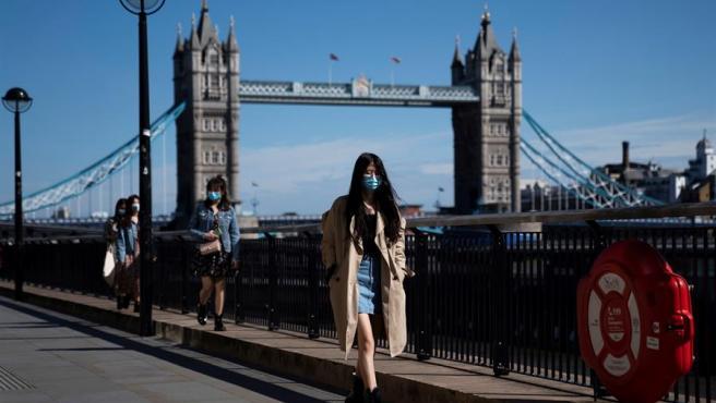 Varias personas con mascarillas por la pandemia del coronavirus caminan junto al Puente de la Torre, en Londres.