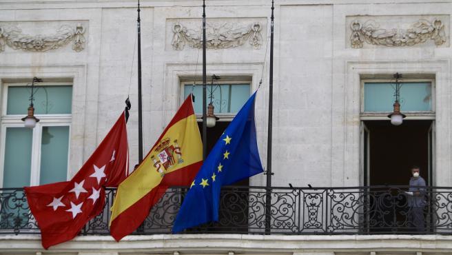 Las banderas lucen a media hasta, en la Real Casa de Correos, sede de la Comunidad de Madrid, en recuerdo de los más de 25.000 fallecidos en España por la pandemia de coronavirus.