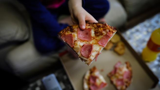 Un niño sostiene un trozo de pizza del menú infantil de Telepizza en el barrio de San Fermín en el distrito de Usera, cadena que, junto a Rodilla, reparte un menú escolar a más de 11.500 alumnos beneficiarios de beca comedor en la Comunidad de Madrid.