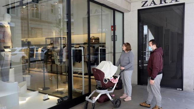 Dos clientes aguardan ante una de las tiendas de Zara que ha abierto sus puertas en Santiago de Compostela, este jueves.