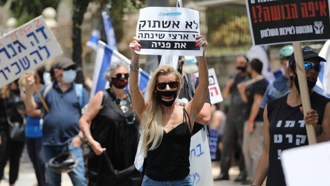 Manifestantes con mascarillas por el coronavirus exigen en Jerusalén que el Tribunal Supremo de Israel falle en contra del nombramiento de Benjamin Netanyahu como primer ministro.
