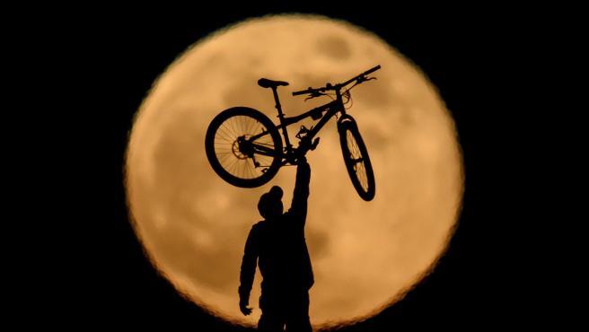 La figura de un ciclista se interpone con la 'Luna llena de mayo', en la localidad húngara de Salgotarjan.