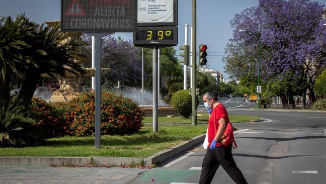Un hombre protegido con guantes y mascarilla cruza por un paso de cebra ante un panel informativo sobre la alerta de coronavirus y un termómetro que marca 39 grados en Sevilla.