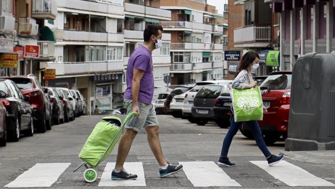 Un hombre caminando con un carrito de la compra.