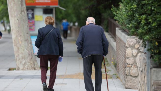 Una mujer de edad avanzada pasa al lado de un hombre con bastón que pasea por la capital en su franja horaria permitida