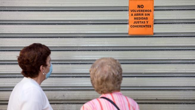 Dos mujeres leen un cartel puesto en una persiana echada de un comercio de Málaga.