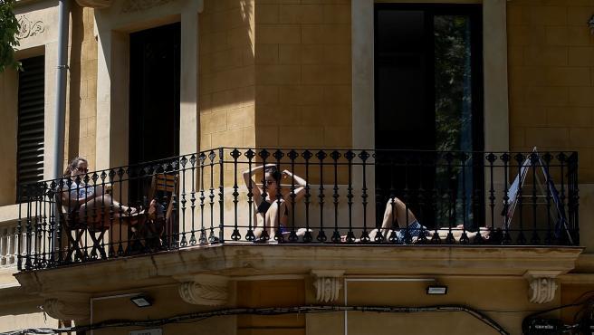 Tres jóvenes toman el sol en el balcón durante el confinamiento en Barcelona.