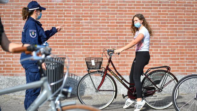 Una agente de Policía habla con una mujer con mascarilla en Milán.
