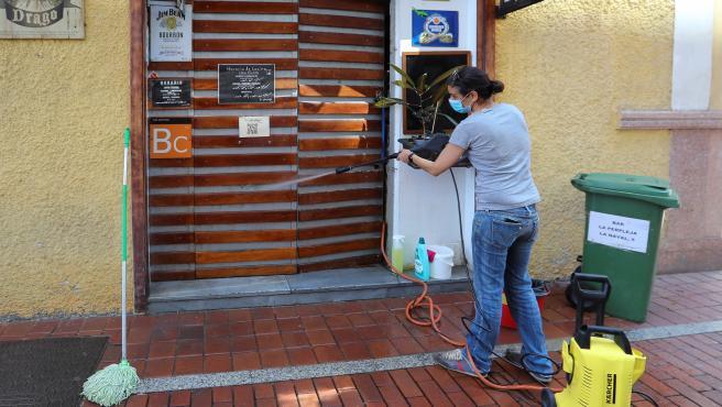 La propietaria de un gastrobar de Las Palmas de Gran Canaria prepara su local para reabrir, ante el inicio de la fase 1 de la desescalada del confinamiento por el coronavirus.