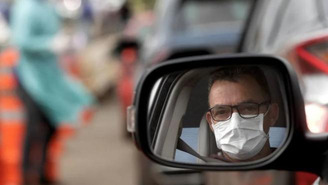 Un hombre llevando mascarilla en su coche.