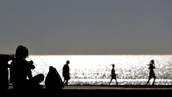 Varias personas disfrutan de un paseo, a primera hora, en la playa de la Malvarrosa en el horario establecido, tras no haber pasado a la fase 1.