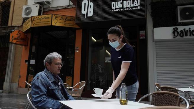 Una camarera atiende a un señor en la terraza de un bar en el centro de Córdoba, este lunes, cuando comienza la fase 1 de la desescalada en la provincia.