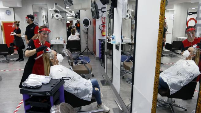 MLG 04-05-2020.-Primer día de apertura de los comercios con cita previa en el inicio de la Fase 0 de la desescalada, en la imágen una clienta en una peluquería de la capital.-ÁLEX ZEA.