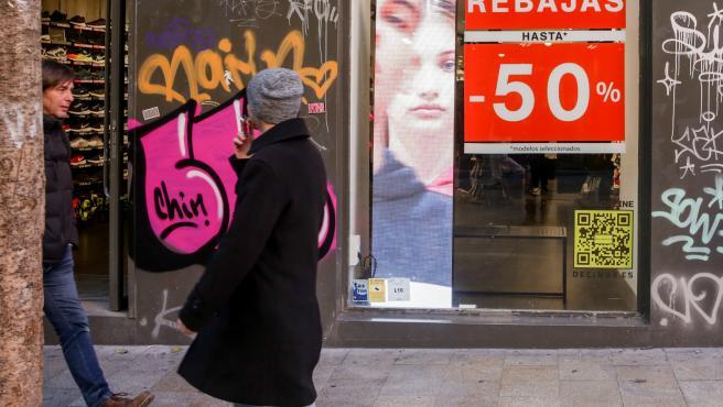 Dos hombres pasean junto a una tienda en Madrid, en la que se ofertan rebajas de hasta un 50%.