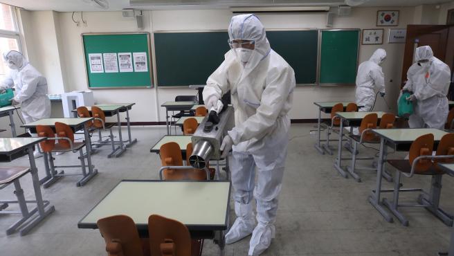 Un equipo de trabajadores, con trajes de protección, desinfecta todo el mobiliario de una clase, en un colegio de Seúl (Corea del Sur).