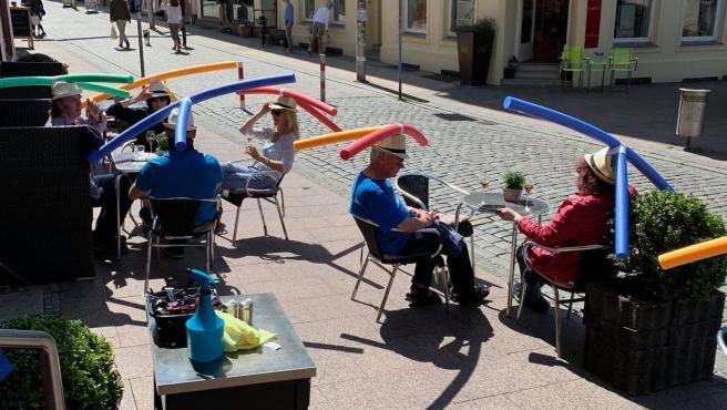 Terraza de un bar de Alemania donde usan sombreros con churros de piscina para mantener las distancias de seguridad.