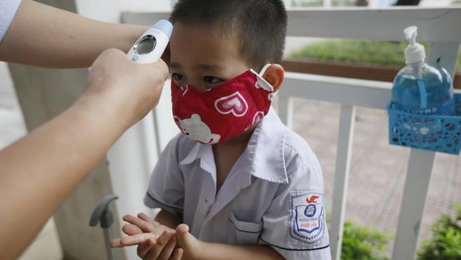 Un niño espera que le tomen la temperatura, antes de acceder a su colegio, en Hanoi (Vietnam).