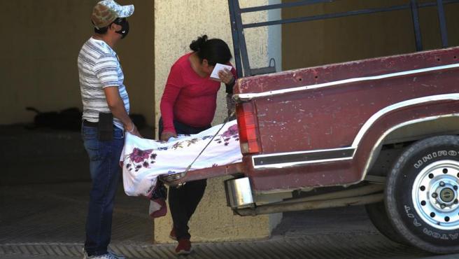 Dos personas permanecen junto al cuerpo de un hombre de 75 años que murió por COVID-19 al llegar a un hospital en Ciudad Juárez, México.
