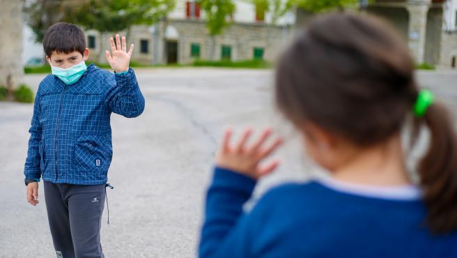 Dos niños se saludan durante un paseo por Madrid.