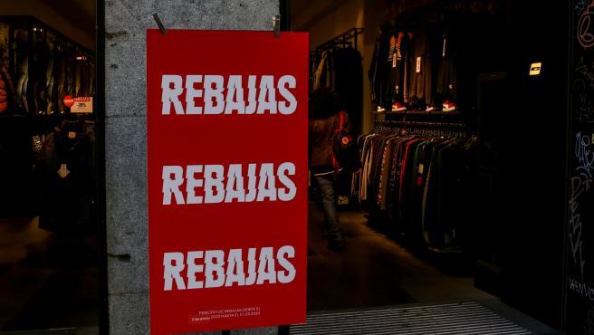 Un cartel en la entrada de una tienda de moda en el que se lee ' Rebajas'.