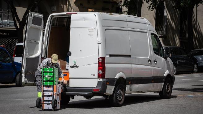 Un repartidor descarga material de una furgoneta