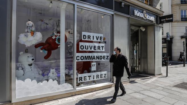 Un hombre camina junto a una tienda abierta en París