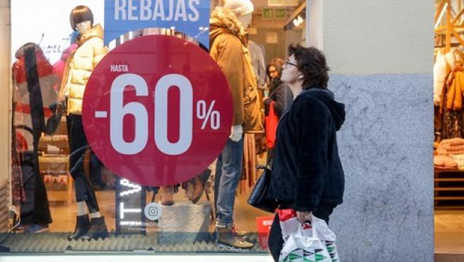 Una mujer pasea junto a una tienda de moda de Madrid, en la que se ofertan las segundas rebajas con ofertas de hasta el 60%.