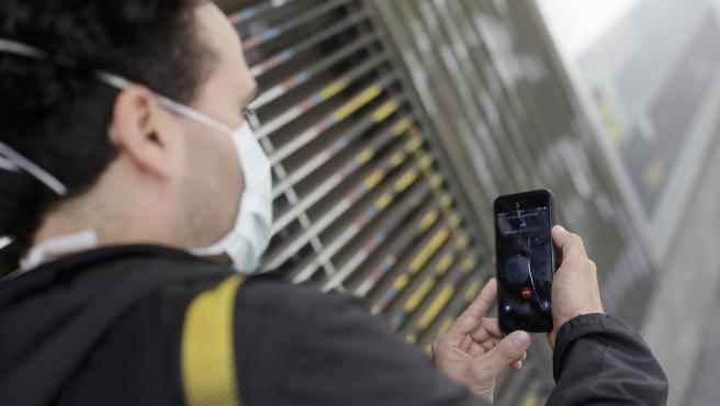 Un hombre protegido con mascarilla realiza una videollamada por su teléfono móvil, una de las formas más habituales de comunicarse durante la pandemia del coronavirus ya que permite tener más 'cerca' a familiares y amigos. En Madrid, (España), a 24 de abr