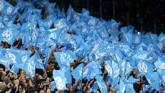 Decenas de aficionados del Olympique de Marsella mueven banderas azules, el color del equipo francés, durante una partido en el estadio Velodrome.