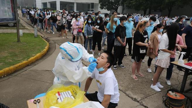Un sanitario toma muestras a un trabajador para un test del coronavirus en una fábrica en Wuhan, China, dentro de un plan para realizar pruebas de COVID-19 a los más de 10 millones de habitantes de la ciudad.