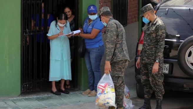 Un militar carga una ración de comida para una familia en el barrio desfavorecido de La Betania, en Tegucigalpa, Honduras, durante la pandemia del coronavirus.