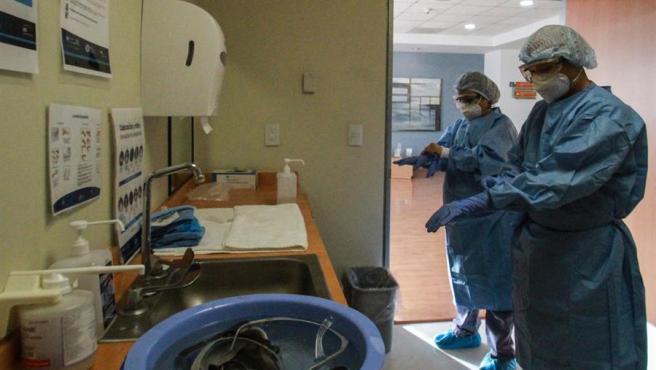 Dos médicos se ajustan sus trajes de protección antes de entrar en la UCI para revisar a un paciente de COVID-19, en un hospital de Tijuana, México.