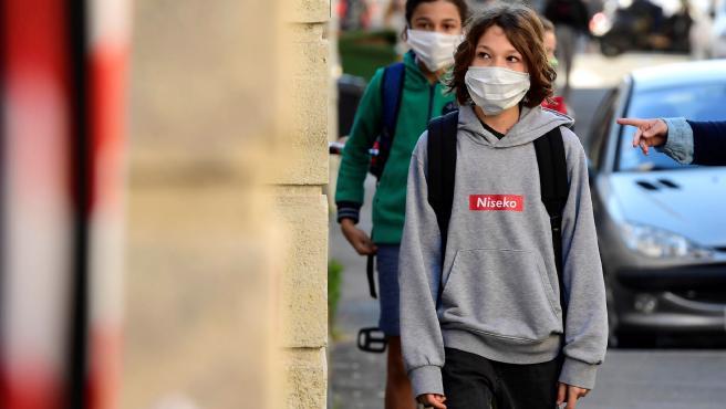 Estudiantes esperan fuera de una escuela en Burdeos.