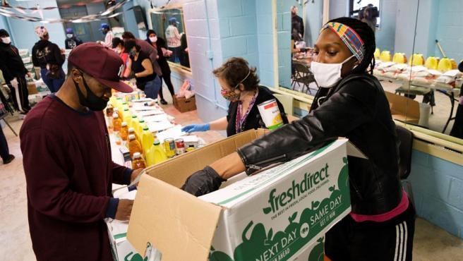 Voluntarios organizan la distribución de comida entre personas necesitadas de una zona de viviendas públicas en Nueva York, durante la pandemia del coronavirus.