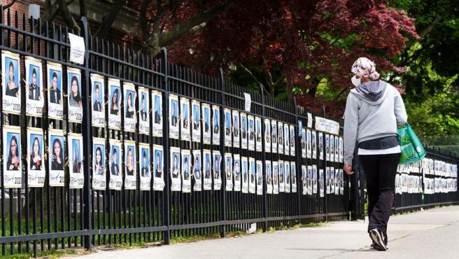 Fotos de alumnos del último curso de secundaria de un instituto de Brooklyn, en Nueva York, colocadas en la verja del centro para sustituir la ceremonia de graduación, suspendida por la pandemia del coronavirus.
