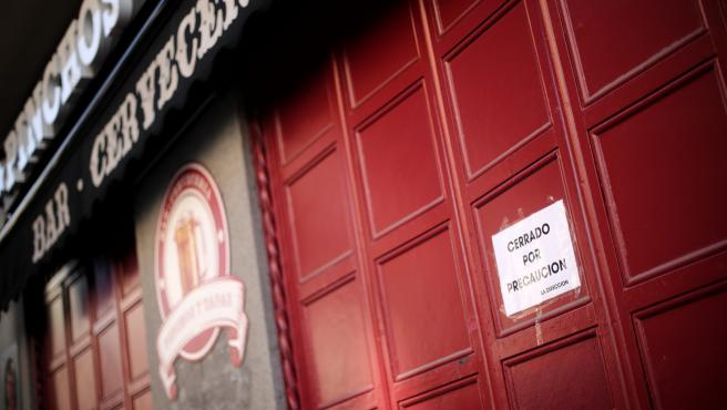 Entrada cerrada de un bar en el que un cartel dice 'Cerrado por precaución' (archivo)