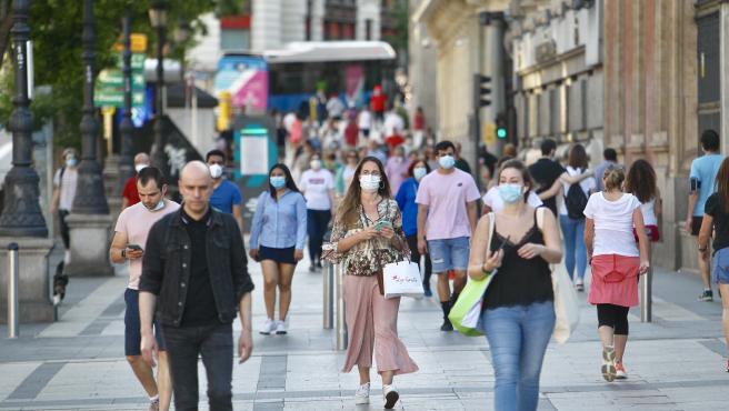 Personas paseando con mascarilla por Madrid.