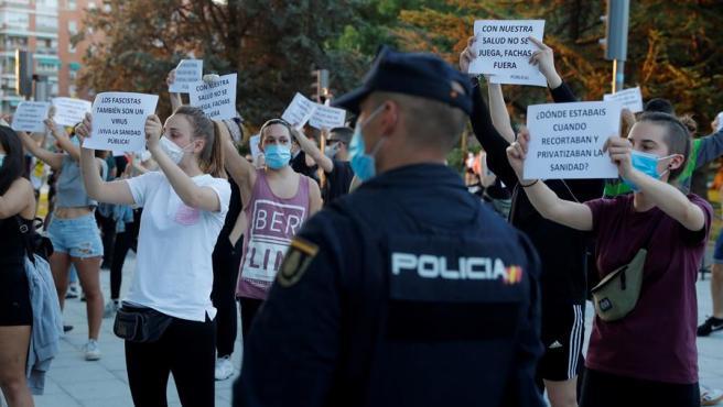 Ciudadanos ataviados con mascarillas muestran carteles durante una concentración a favor de la sanidad pública, este jueves en Moratalaz, Madrid.