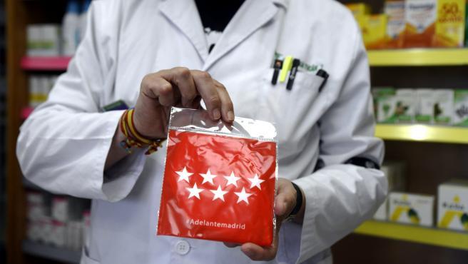 Un cliente coge en sus manos una de las siete millones de mascarillas FFP2 modelo KN95 que a partir de este lunes reparten las farmacias entre la población de la Comunidad de Madrid.